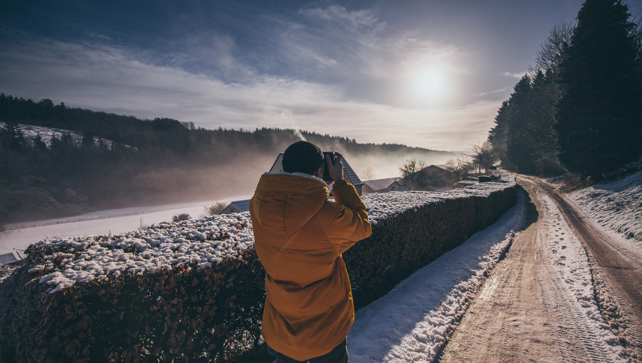 Man Photographing Landscape Standing On A Snowy Path.