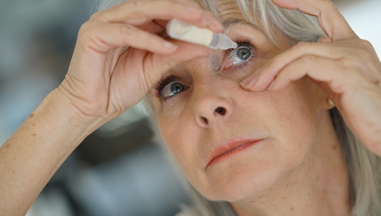 Older Woman Putting Eye Drops Into Her Dry Eyes.