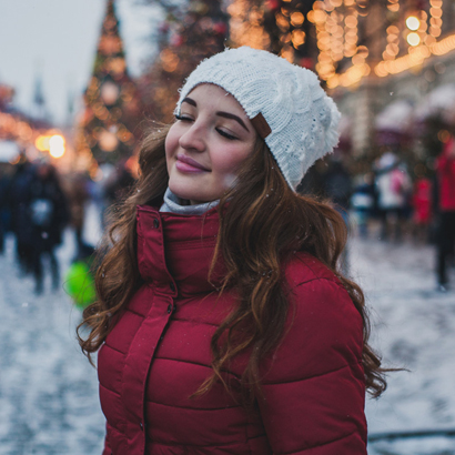 Woman Smiling With Eyes Closed In The Snow.