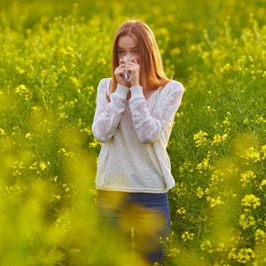 Woman Blowing Nose In Field Of Flowers.