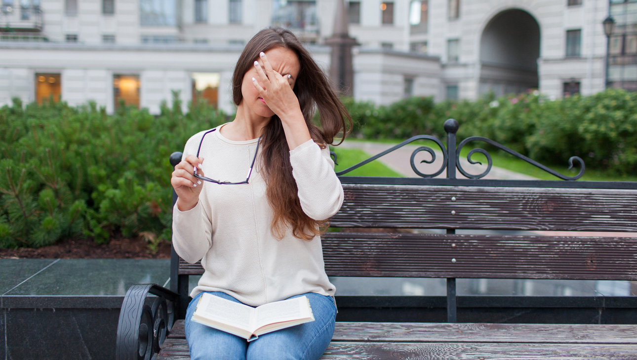 Woman Rubbing Her Eyes While Sitting On A Bench.